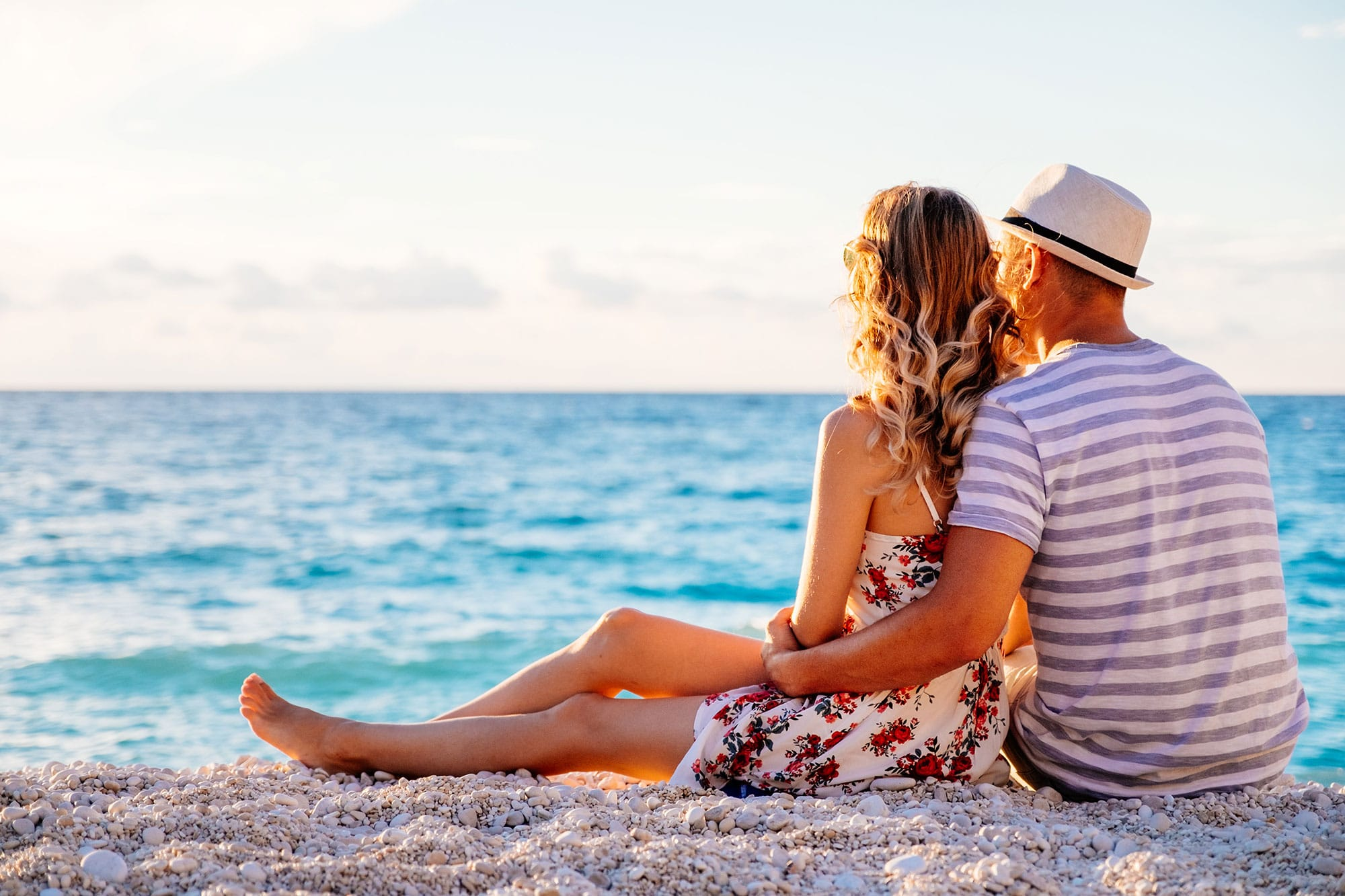 young-couple-in-love-sitting-on-the-beach-