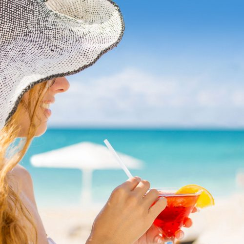 Woman drinking a cocktail on the beach on a sunny day