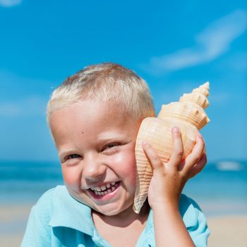 Kid on the beach with conch on his ear